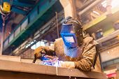 image of protective eyewear  - Young man with protective mask welding in a factory - JPG