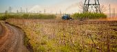 stock photo of plowing  - The blue tractor plowing a field with a dust trace behind a plow against an industrial landscape - JPG