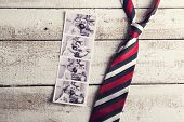 stock photo of polaroid  - Polaroid pictures of father and daughter and colorful tie laid on wooden floor backround - JPG
