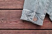 image of jacket  - sleeve of a jeans jacket sleeve of a jacket of jeans on a wooden background - JPG