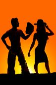 stock photo of cowgirls  - A silhouette of a cowgirl with her cowboy in the outdoors - JPG