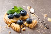 pic of curd  - Shortbread home made broken tartlet filled with lime curd and blueberries on old vintage metal background - JPG