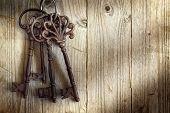 stock photo of skeleton key  - Old skeleton keys hanging against a wooden background - JPG