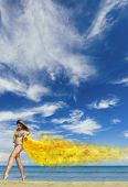 stock photo of windy  - Young woman in bikini holding a yellow sarong on windy beach - JPG