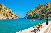 image of greek-island  - Amazing view on  bench, isthmus and clear sea view in small cosy port of Vathi on Greek Kalymos Island, Greece ** Note: Soft Focus at 100%, best at smaller sizes - JPG