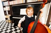 pic of cello  - Happy kid in school uniform dress playing on the cello sitting near the piano and shelves with books - JPG