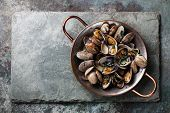 picture of slating  - Shells vongole venus clams in copper cooking dish on stone slate background - JPG
