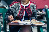 pic of smoking woman  - A young woman is eating cokcles and smoked fish outside on a sunny day - JPG