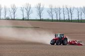 picture of cultivator-harrow  - The tractor harrowing the large brown field in spring season - JPG