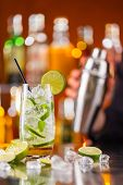 stock photo of mojito  - Mojito cocktail drink on bar counter with barman holding shaker on background - JPG