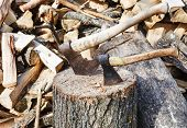 image of cleaving  - stack of wood deck for chopping firewood two axes on rustic courtyard - JPG