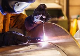 image of welding  - Young man with protective mask welding in a factory - JPG
