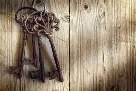 stock photo of skeleton key  - Old skeleton keys hanging against a wooden background - JPG