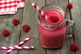 stock photo of smoothies  - Pink raspberry smoothie in a mason jar with straws on a rustic wood background - JPG