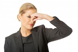 stock photo of disgusting  - Woman pinching her nose because of disgusting smell - JPG