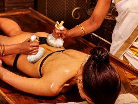 stock photo of panchakarma  - Woman having ayurvedic massage with pouch of rice - JPG