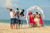 Bride standing with bridesmaids under archway on beach and waiting for her drunk groom