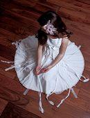 Girl Wearing Neat Dress Sitting On Wooden Floor