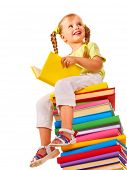 Little girl sitting on stack of books. Isolated.