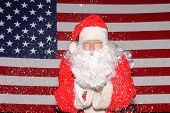 Santa Claus stands in front of the American Flag. Santa Claus Blows Snow or Glitter from his hands w poster