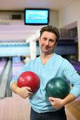 Man stands in club and holds two balls for bowling