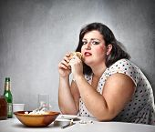 Fat woman feeling guilty while eating junk food