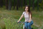 Young Woman Riding On Bicycle In The Forest poster