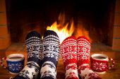 Couple In Christmas Socks Near Fireplace poster