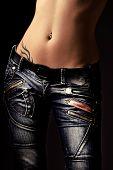 close-up do corpo da mulher em jeans, fundo escuro studio, vertical