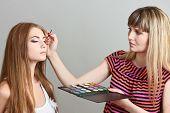 Make-up artist applying eye shadows on beautiful model