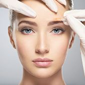 Portrait of young Caucasian woman getting botox cosmetic injection in forehead. Beautiful woman gets poster