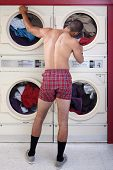picture of partially clothed  - Muscular man in boxer shorts stands waits by a clothes dryer - JPG