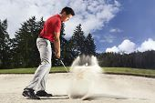Young male golf player in red shirt and grey pants chipping golf ball out of a sand trap with sand wedge and sand caught in motion.