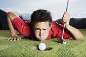 Desperate young male golf player in red shirt and putter lying on golf green and blowing golf ball into cup, focus on ball.