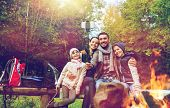 camping, travel, tourism, hike and people concept - happy family sitting on bench and taking picture poster
