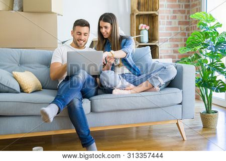 poster of Young couple moving to a new home relaxing sitting on the sofa using computer laptop, smiling happy