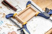 Senior Carpenter Glueing Wooden Craft Surface And Joining With Clamps. Woodwork Carpenter With Equip poster