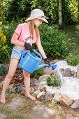 Little girl helping parents in a summer garden watering miniature Juniper tree at alpine rock garden poster