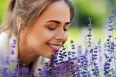 gardening and people concept - close up of happy young woman smelling lavender flowers at summer gar poster