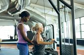 Side view of young fit African-american female trainer assisting active senior Caucasian  woman on l poster