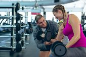 Front view of handsome Caucasian male trainer assisting fit Caucasian female athlete to exercise wit poster