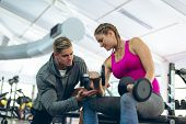 Low angle view of handsome young Caucasian male trainer assisting fit young Caucasian female athlete poster