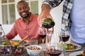 Closeup of senior man hand pouring red wine in glass. Host man serving alcohol during lunch with fri poster