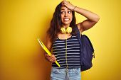 Student woman wearing bakcpack notebook headphones over isolated yellow background stressed with han poster