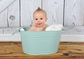image of washtub  - happy baby boy sitting in green washtub - JPG