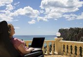 Senior Woman Using Laptop On Holiday