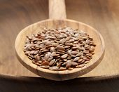 stock photo of flax seed  - wooden spoonful of flax seeds on a wooden bowl - JPG