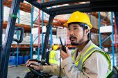Portrait close-up of mature Caucasian male worker talking on walkie-talkie while driving forklift in poster