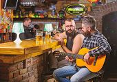 Hipster Brutal Bearded Spend Leisure With Friend In Bar. Man Play Guitar In Bar. Cheerful Friends Re poster
