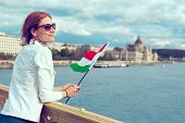Young Redhead Hungarian Urban Woman Holding Hungarian Flag At Budapest poster